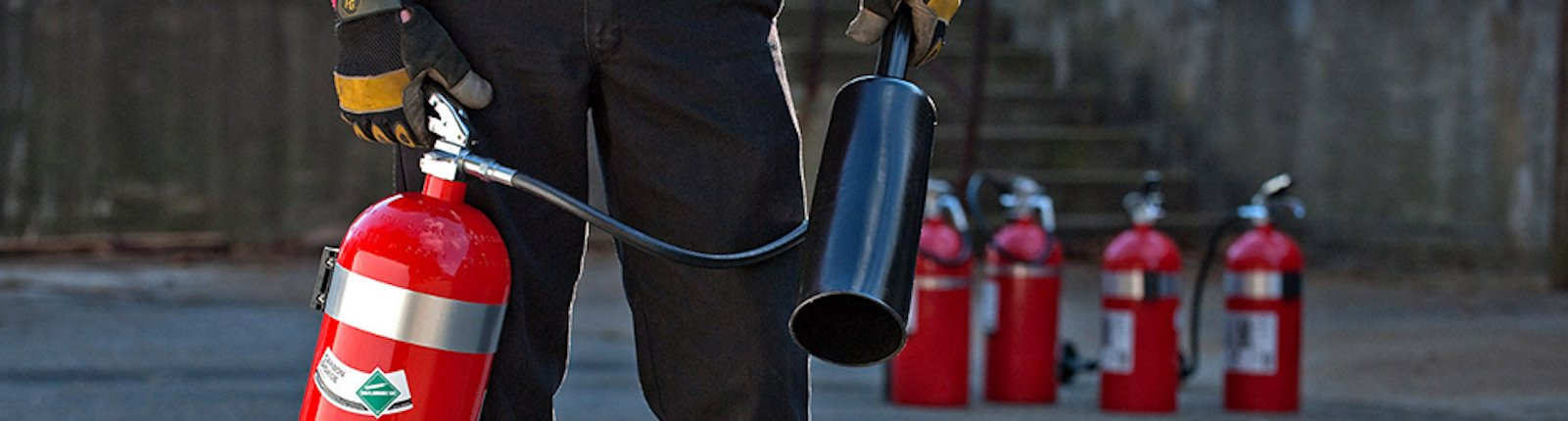 Close up of technician holding fire extinguisher