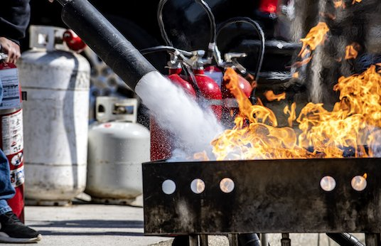 Man using fire extinguisher to put out controlled fire