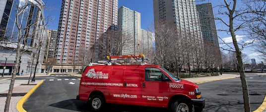 City Fire van in front of multi-family buildings