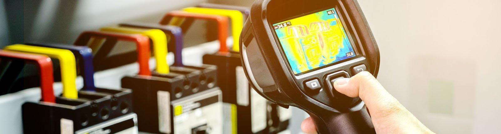 Close-up of hand using thermal imaging camera to check temperature