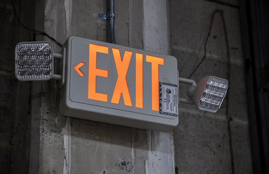 Close up of emergency exit sign with lights on wall